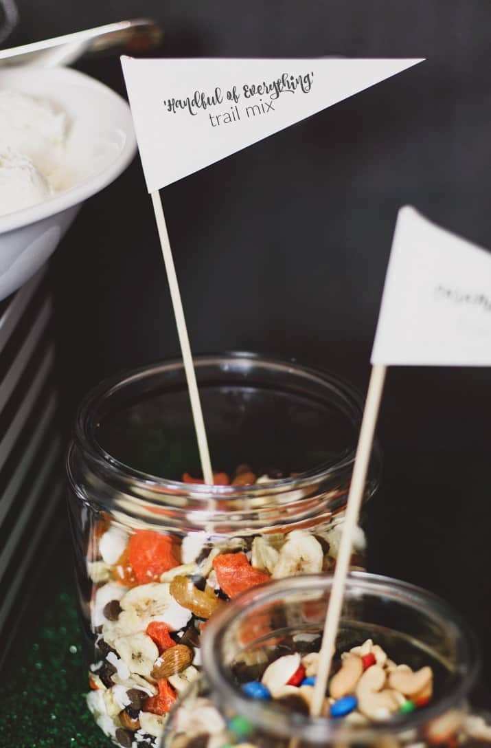 game day ice cream bar with dried fruit toppings in glass canister