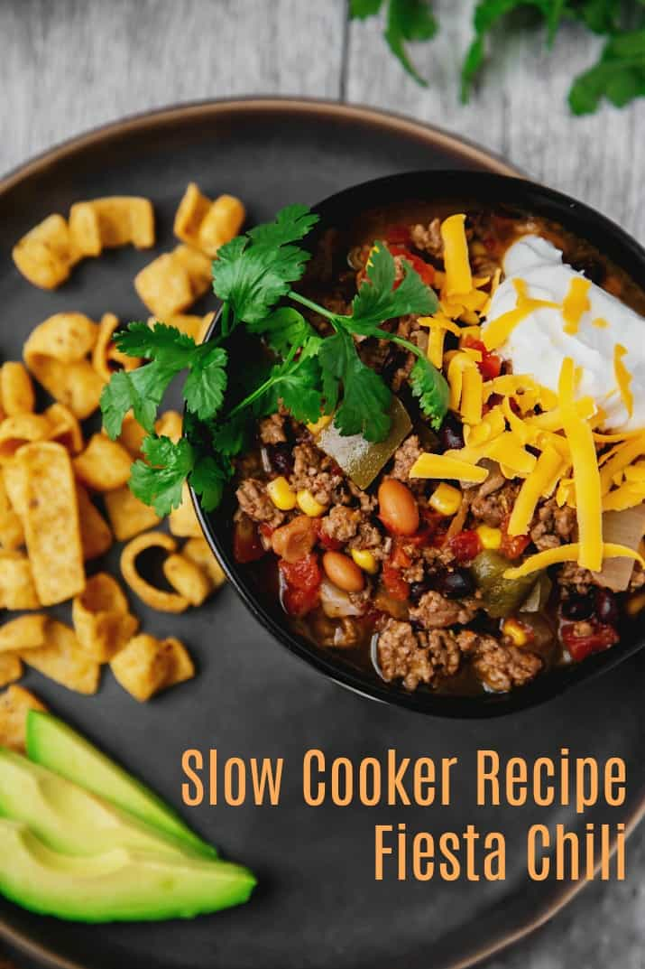 easy fiesta chili recipe in black bowl on gray plate, overhead view with text
