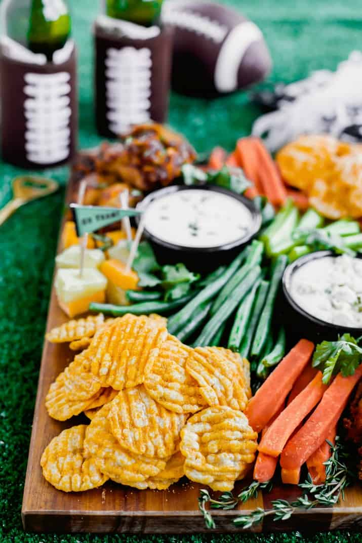 game day football party snack board with chips, vegetables, and wings