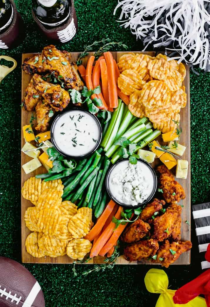game day football party snack board on turf mat with football paraphernalia