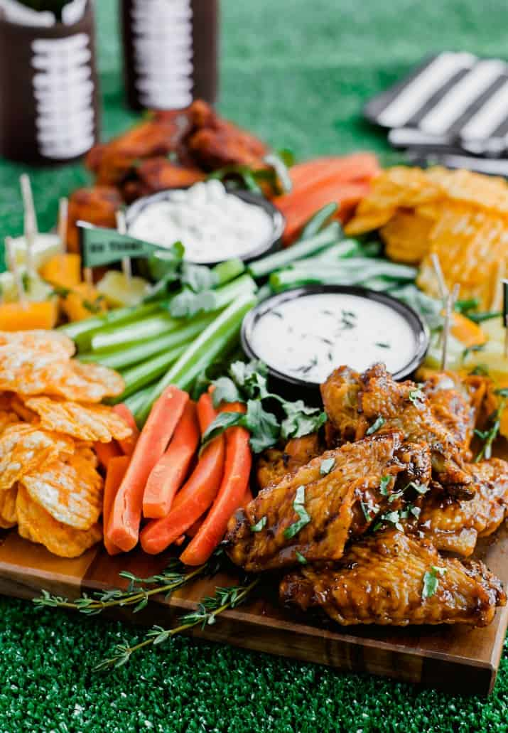 game day football party snack board with wings, chips, and crudites