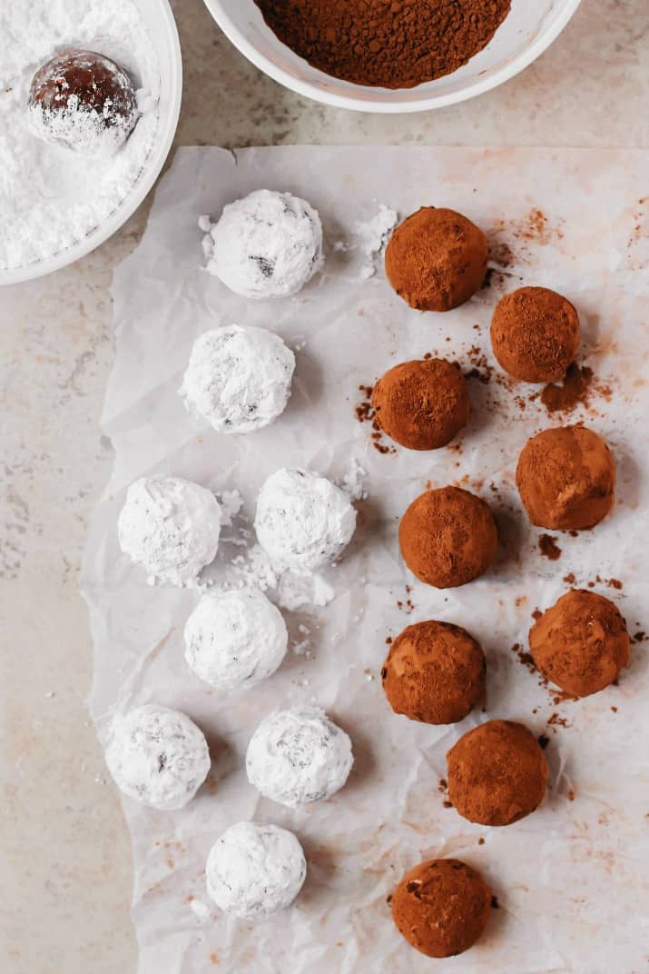 bourbon balls recipe coated in cocoa and powdered sugar with bowls
