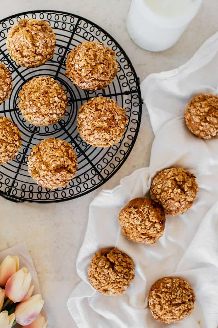 spice muffins with oatmeal topping on round cooling rack and on white towel, overhead view