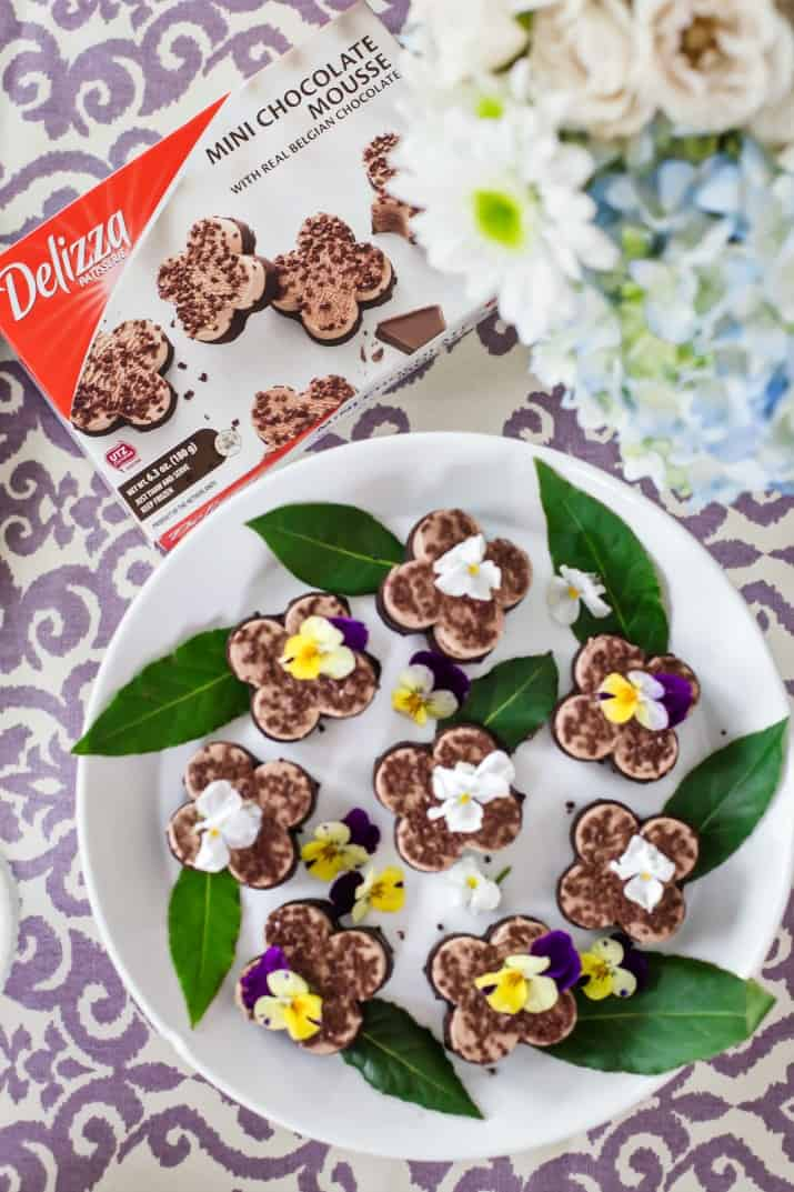 dessert platter of mini chocolate mousse topped with pansies, with Delizza box