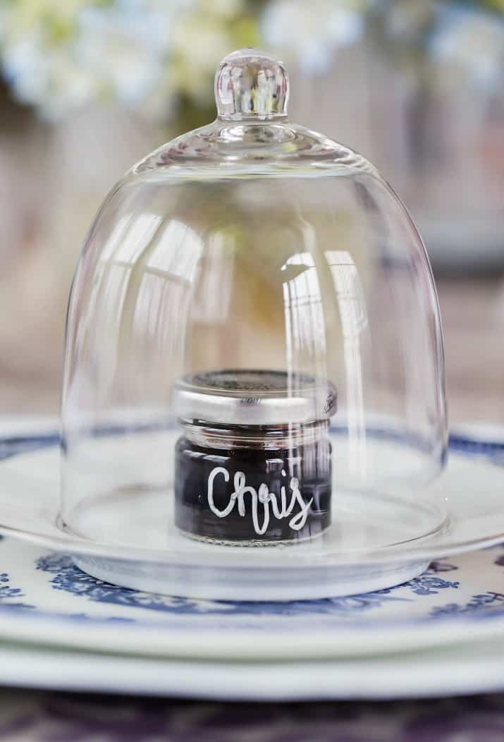 mini jelly jars with name written on it, under glass dome