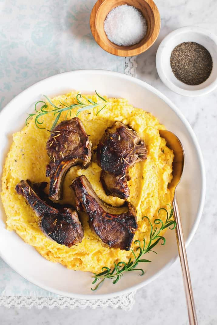 Lamb Chops with Goat Cheese Polenta in white bowl on blue napkin, overhead view