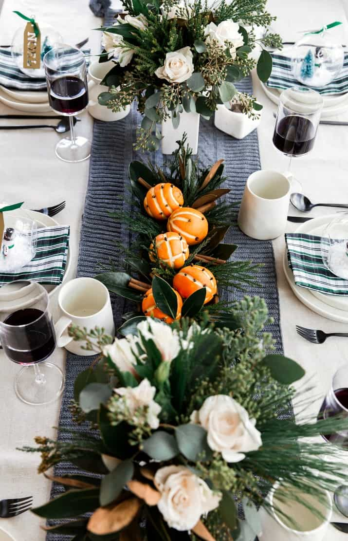 Christmas table centerpiece with greenery and pomanders