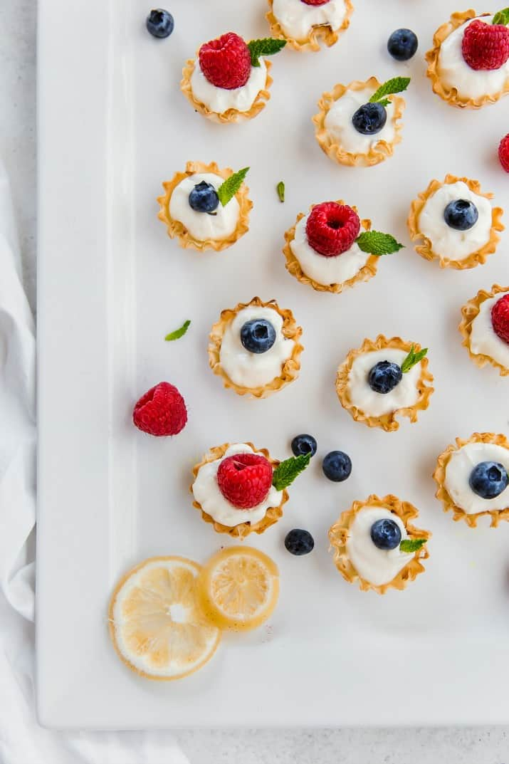 easy lemon tartlet dessert recipe in phyllo cups, topped with fresh berries
