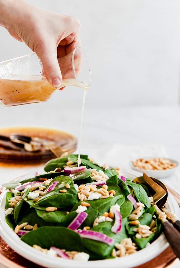 pouring dressing on spinach salad