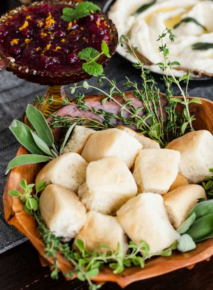 Thanksgiving rolls in wood bowl garnished with fresh herbs