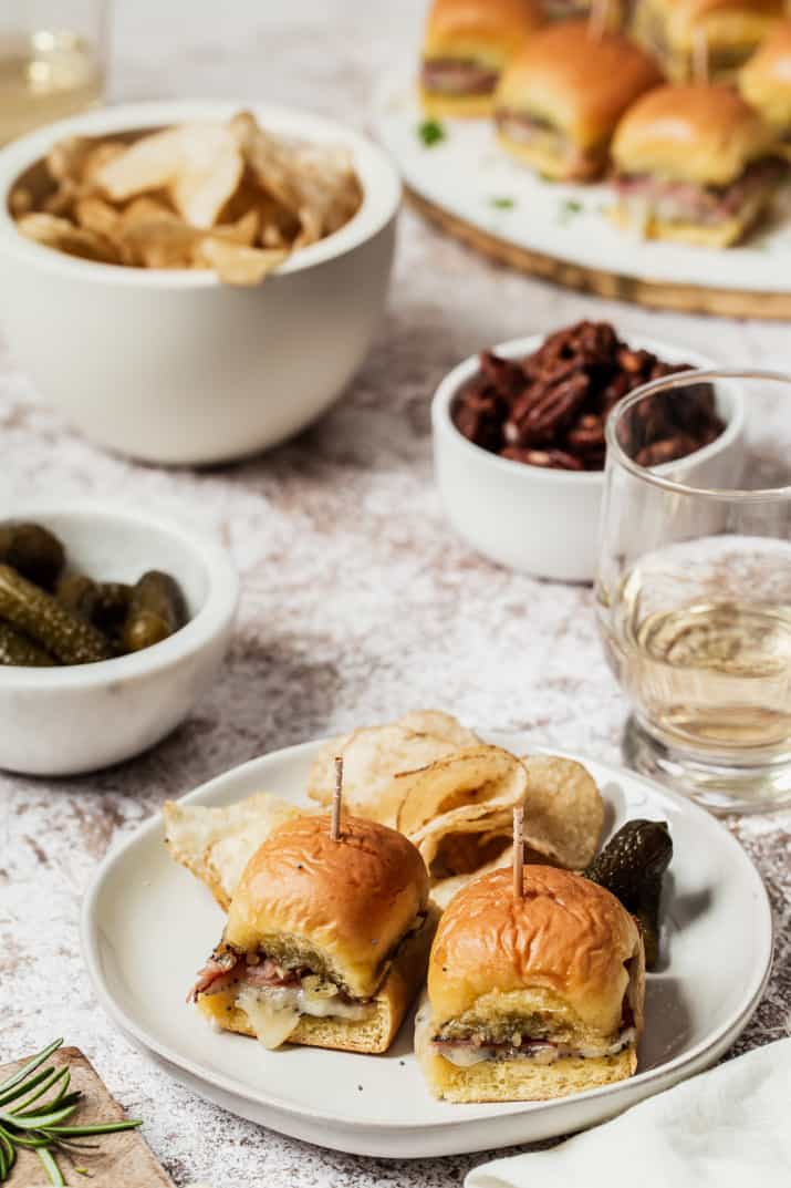 two ham and cheese sliders on white plate on party table
