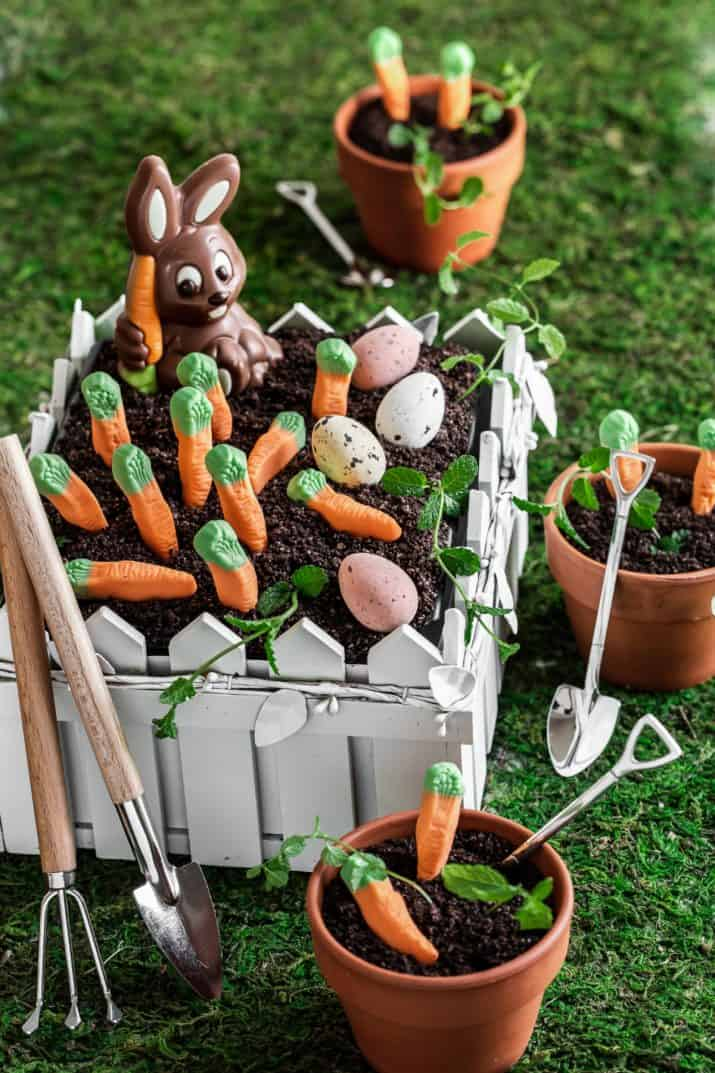 dirt cake in white fenced garden container, decorated with chocolate bunny, candy carrots, and chocolate eggs.