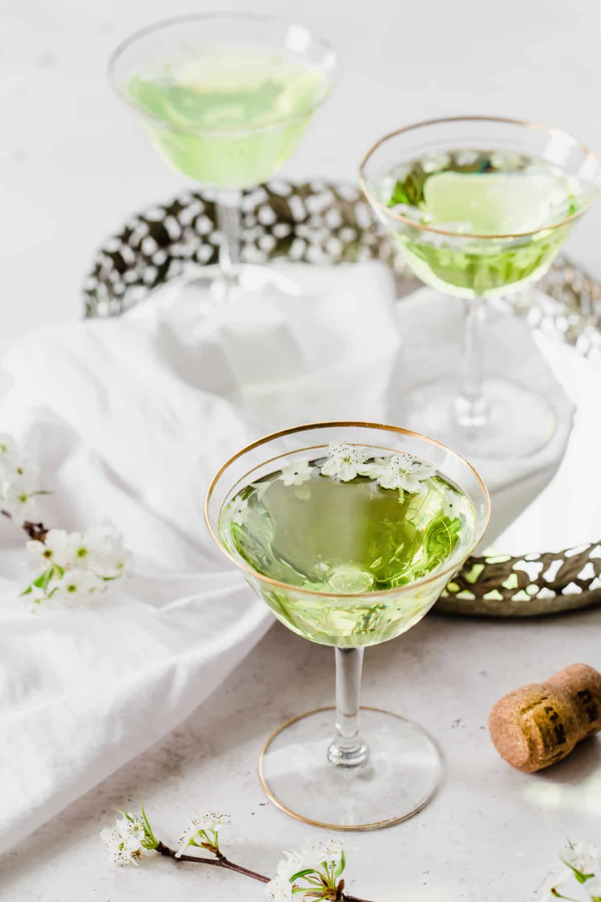3 coupes with green cocktails, on white table