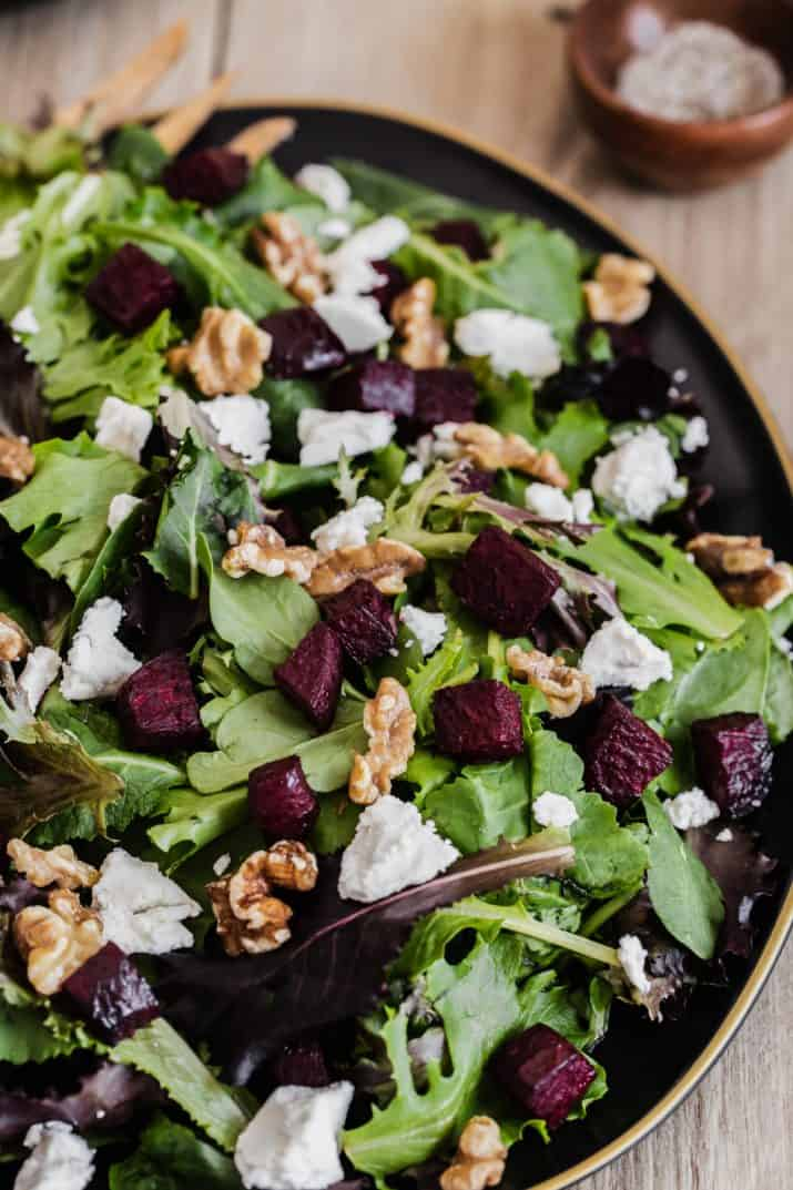 close up overhead view of green salad with roasted beets and goat cheese