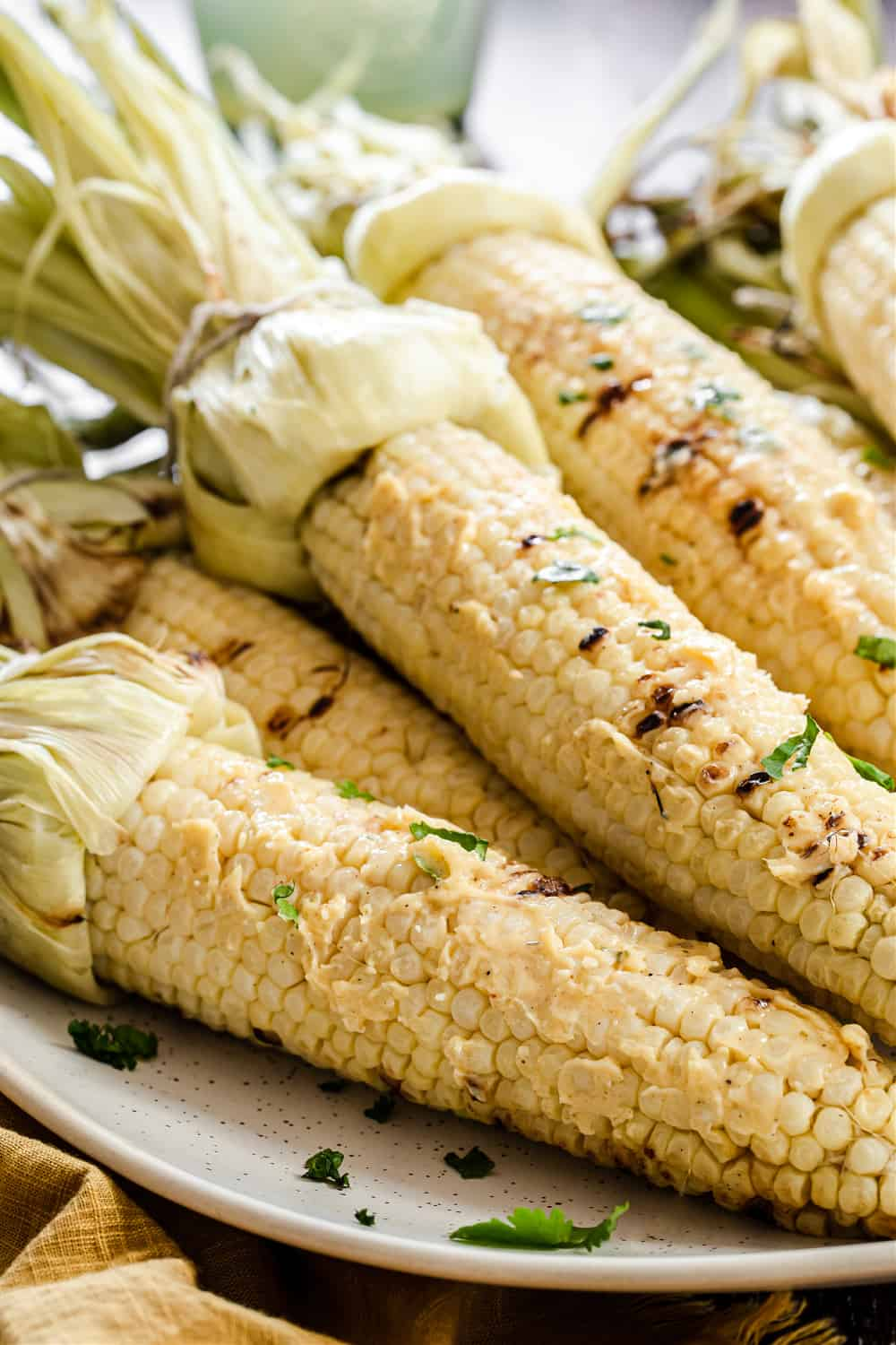 grilled corn on the cop with husks attached, slathered in butter