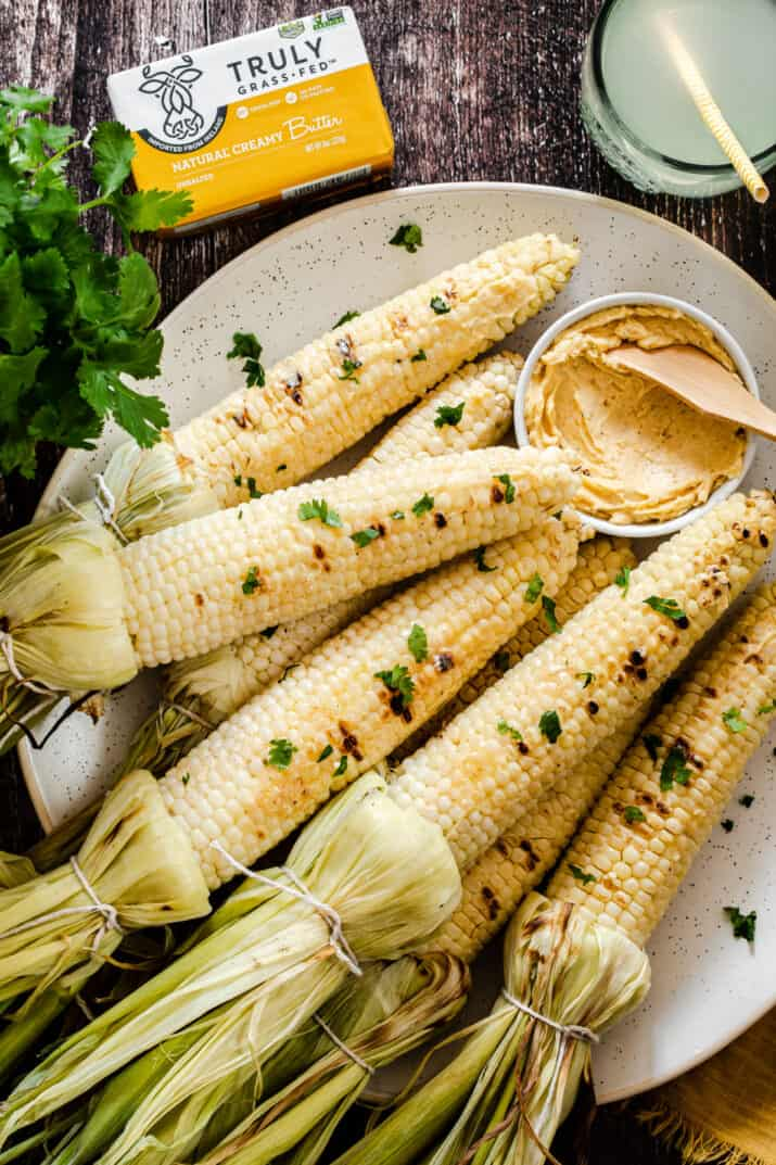 grilled corn on the cob on white platter with butter in bowl