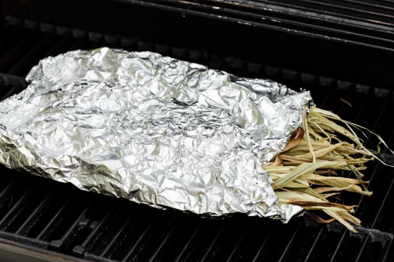 corn wrapped in foil on grill