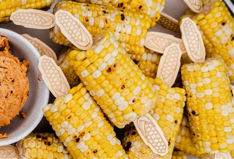 roasted corn on the cop with corn picks attached