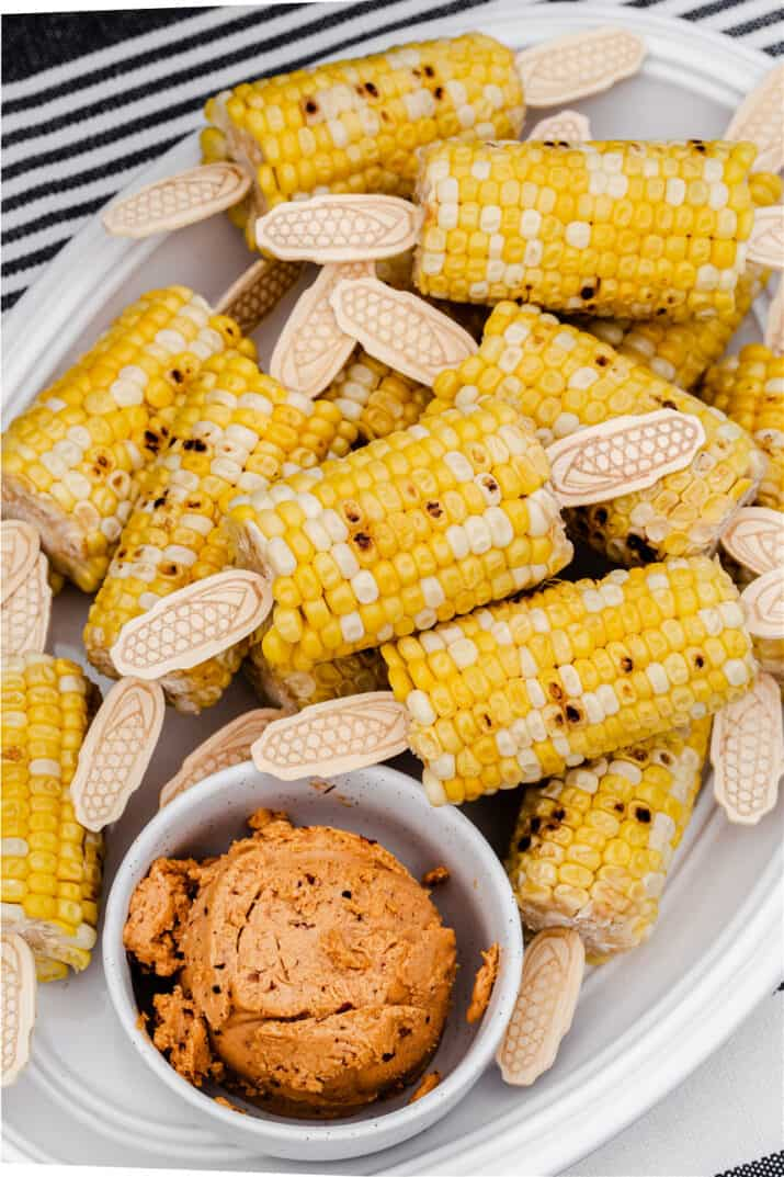 corn on the cob with flavored butter, on white plate