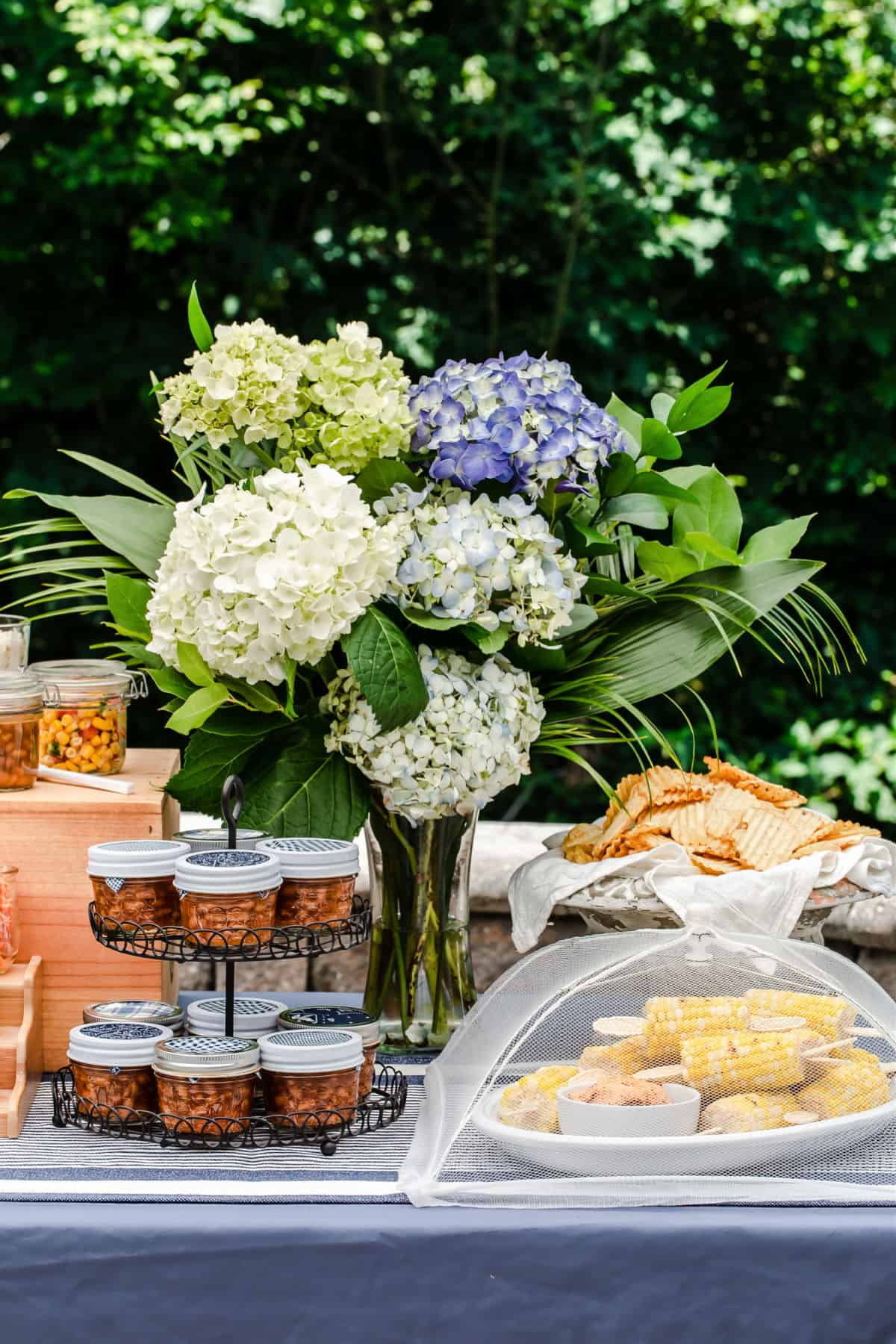 outside party table with jars of bean, corn, and flowers