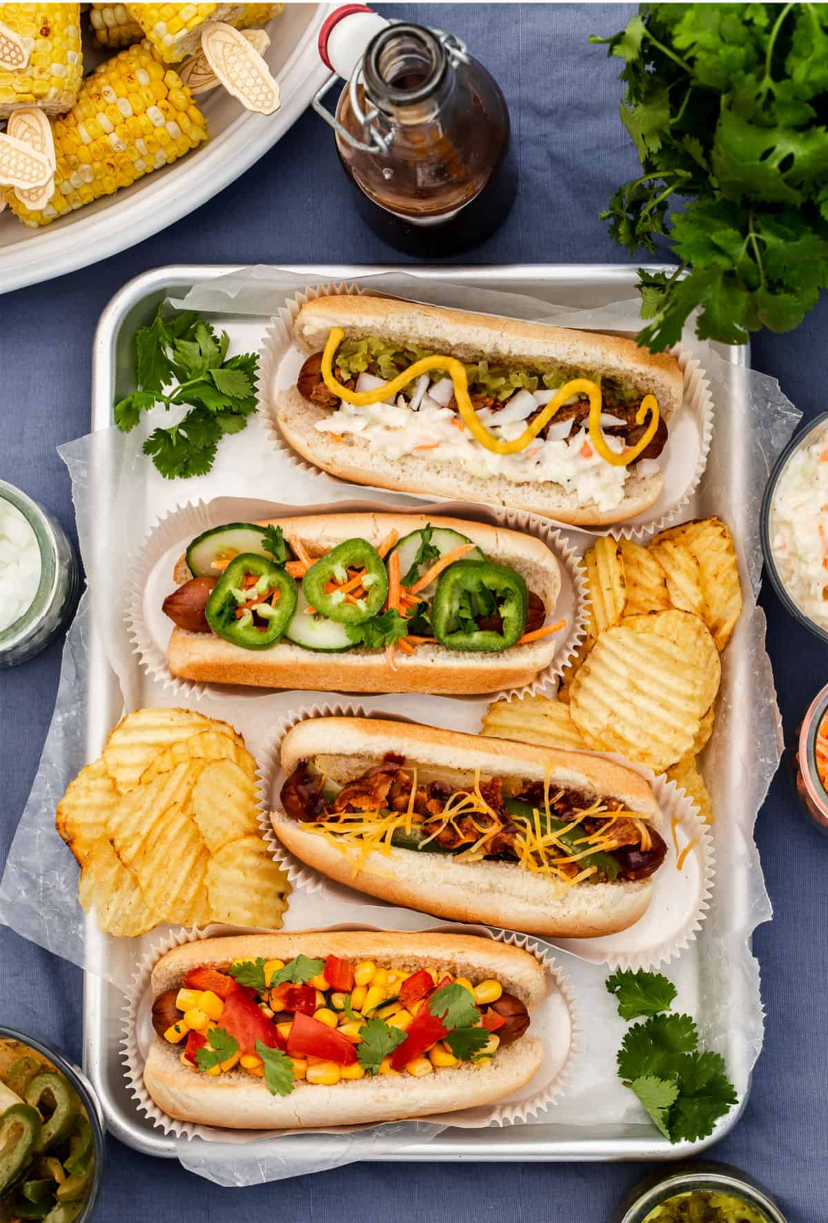 4 hot dogs on a pan, topped in different ways