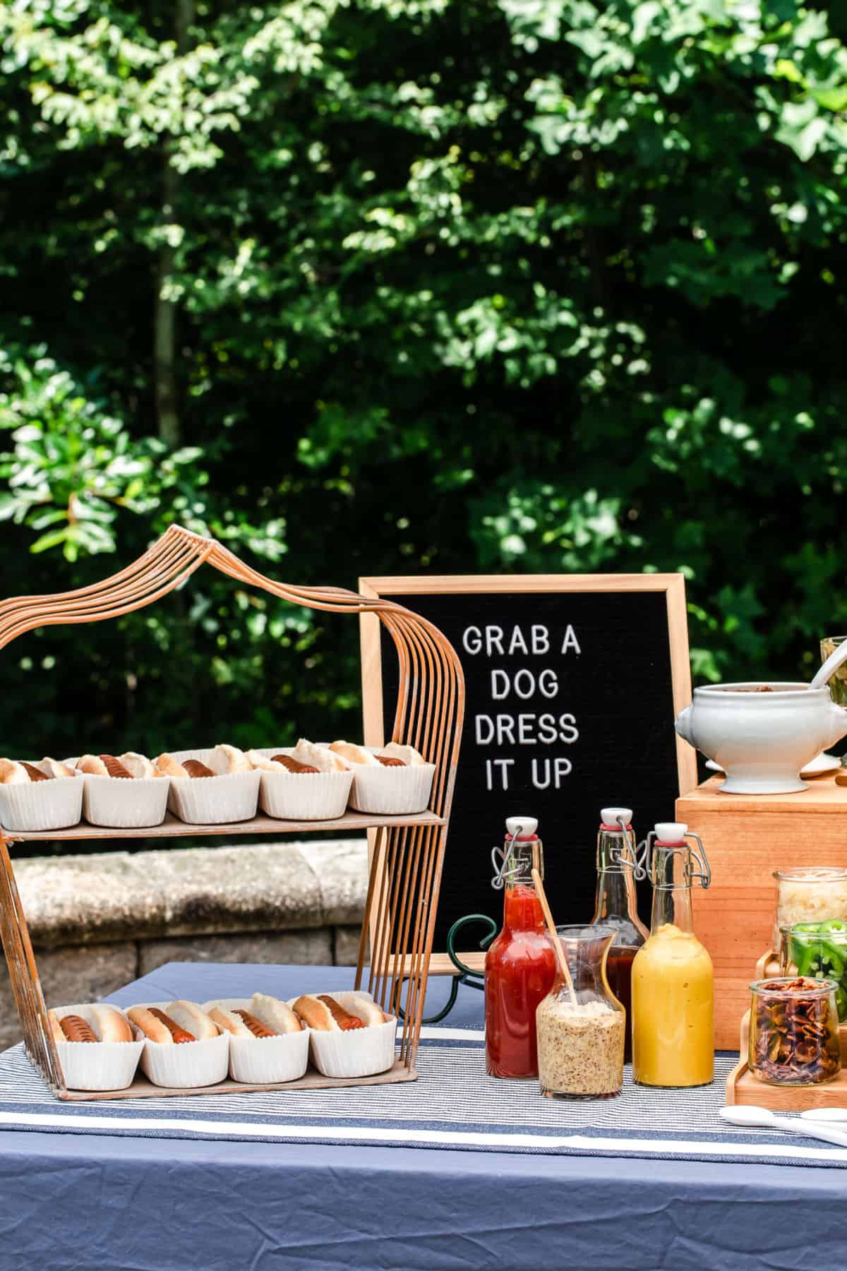 party table with hot dogs on wire stand and hot dog sign