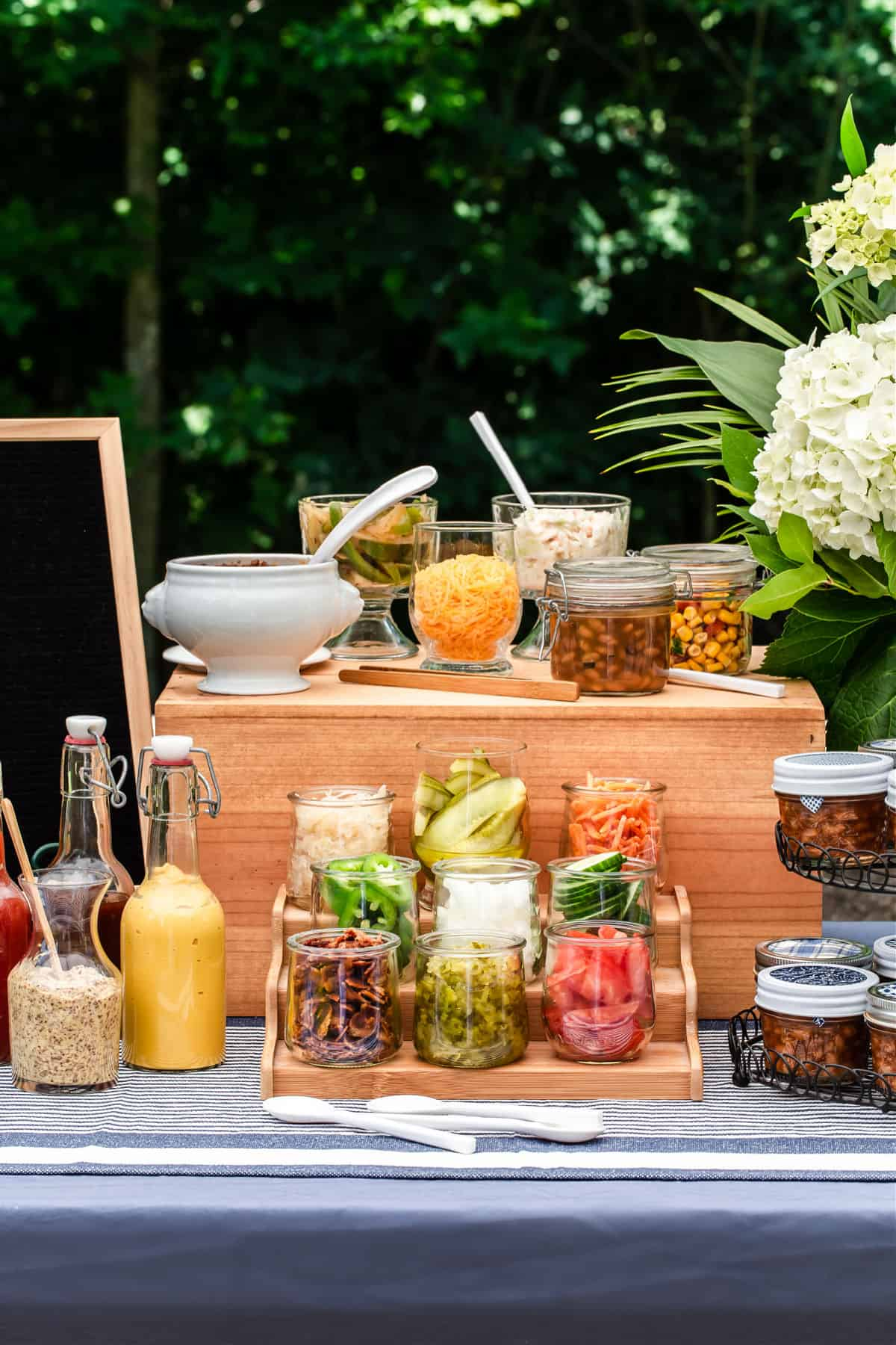hot dog toppings in jars and bottles, on party table
